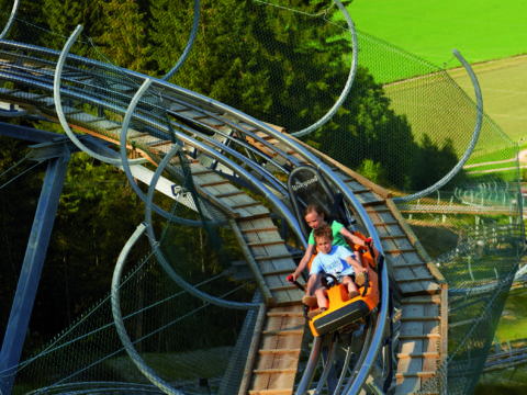 Kinder beim Sommerrodeln auf dem Lucky Flitzer Alpine Coaster Flachau im Sommer in der Nähe vom JUFA Hotel Altenmarkt. Der Ort für erholsamen Familienurlaub und einen unvergesslichen Winter- und Wanderurlaub.