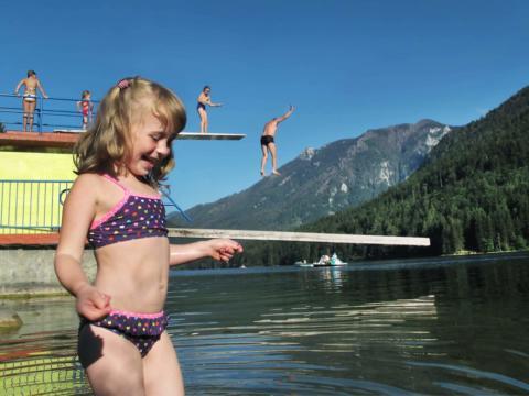 Sie sehen ein Mädchen am Seebad am Lunzer See mit Sprungturm und Menschen im Hintergrund. JUFA Hotels bietet kinderfreundlichen und erlebnisreichen Urlaub für die ganze Familie.