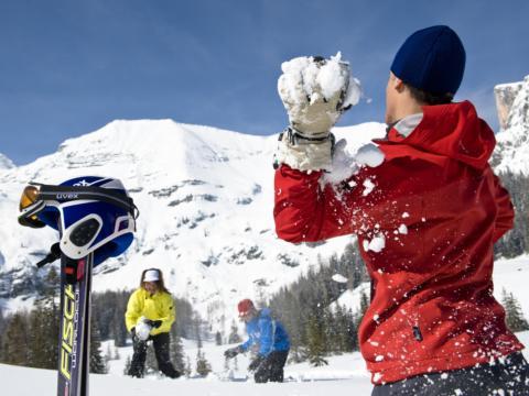 Männer machen eine Schneeballschlacht auf der Wurzeralm bei Pyhrn-Priel. JUFA Hotels bietet erholsamen Familienurlaub und einen unvergesslichen Winterurlaub.