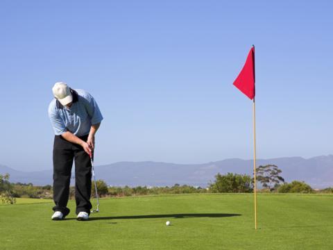 Mann beim Golfen auf Golfplatz im Sommer in der Nähe von JUFA Hotels. Der Ort für erlebnisreichen Natururlaub für die ganze Familie.