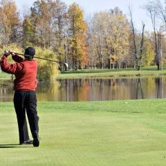 Mann beim Golfen auf Golfplatz mit See im Herbst in der Nähe von JUFA Hotels. Der Ort für erlebnisreichen Natururlaub für die ganze Familie.