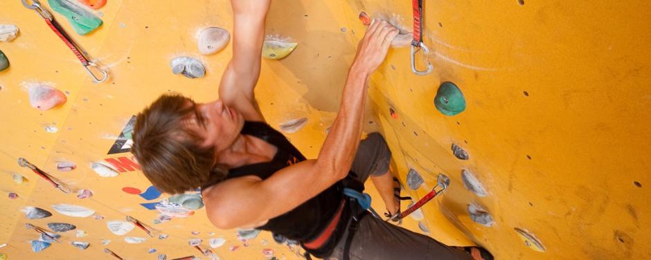 Mann klettert auf Kletterwand im JUFA Hotel Fürstenfeld Sport-Resort. Der Ort für erfolgreiches Training in ungezwungener Atmosphäre für Vereine und Teams.