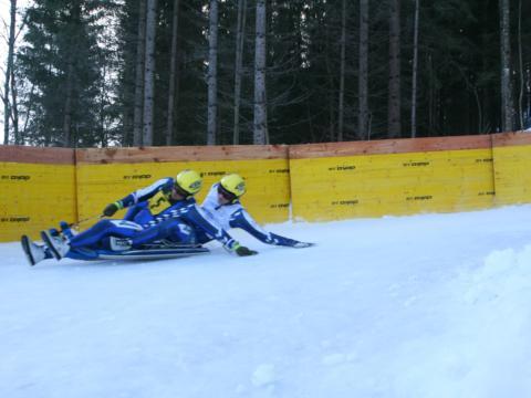 Sie sehen zwei Männer im Zweierbob auf der Naturrodelbahn in Mariazell. JUFA Hotels bietet erholsamen Familienurlaub und einen unvergesslichen Winterurlaub.