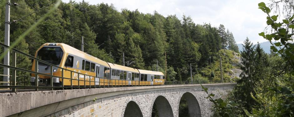 Die Mariazellerbahn, alias die Himmelstreppe, fährt über eine Eisenbahnbrücke durch Landschaft in der Nähe von JUFA Hotels. Der Ort für erholsamen Familienurlaub und einen unvergesslichen Winter- und Wanderurlaub.