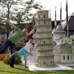 Vater und Sohn lehnen sich an den schiefen Turm von Pisa im Miniformat im Minimundus in Kärnten in der Nähe von JUFA Hotels. Der Ort für erholsamen Familienurlaub und einen unvergesslichen Winter- und Wanderurlaub.