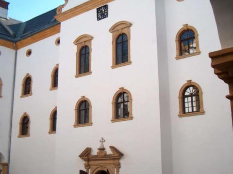 Sie sehen einen Eingang im Innenhof des Schlosses Murau mit alten Fenstern. JUFA Hotels bieten erholsamen Familienurlaub und einen unvergesslichen Winter- und Wanderurlaub