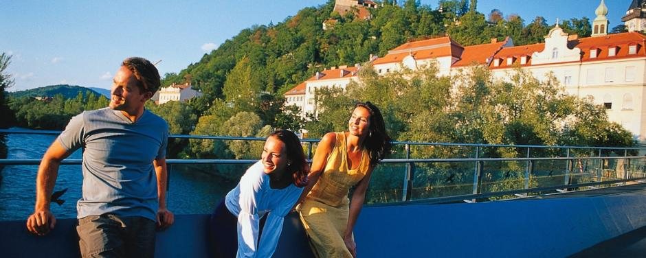 Erwachsene auf dem Mursteg in Graz im Sommer in der Nähe vom JUFA Hotel Graz City. Der Ort für erlebnisreichen Städtetrip für die ganze Familie und der ideale Platz für Ihr Seminar.