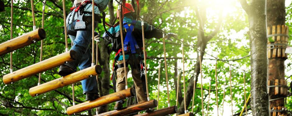 Mutter und Kind beim Klettern im Hochseilgarten im Wald. JUFA Hotels bietet erholsamen Familienurlaub und einen unvergesslichen Winter- und Wanderurlaub.