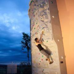 Mann klettert abends im Outdoorsportbereich auf der Kletterwand im JUFA Hotel Fürstenfeld Sport-Resort. Der Ort für erfolgreiches Training in ungezwungener Atmosphäre für Vereine und Teams.
