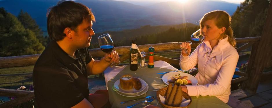 Paar genießt stimmungsvolles Abendessen auf der Tonnerhütte in der Steiermark in der Nähe von JUFA Hotels. Der Ort für erholsamen Familienurlaub und einen unvergesslichen Winter- und Wanderurlaub.