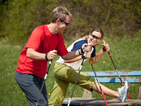 Paar macht Aufwärmübungen vorm Nordic Walking. Der Ort für erholsamen Familienurlaub und einen unvergesslichen Winter- und Wanderurlaub.