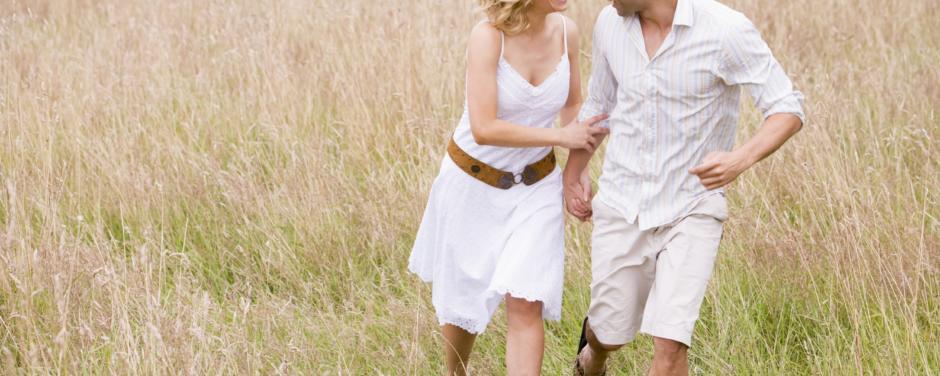 Paar läuft durch Feld im Sommer und genießt die Zeit zu Zweit in der Nähe von JUFA Hotels. Der Ort für erholsamen Familienurlaub und einen unvergesslichen Winter- und Wanderurlaub.