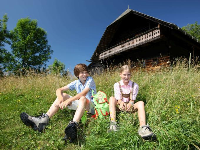 Kinder sitzen in einer Wiese in Peter Roseggers Waldheimat in der Steiermark. JUFA Hotels bietet Ihnen den Ort für erlebnisreichen Natururlaub für die ganze Familie.