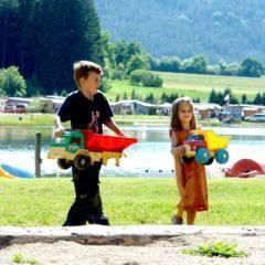 Zwei Kinder mit Sandspielzeug am Badestrand vom Pirkdorfer See in der Nähe von JUFA Hotels. Der Ort für erholsamen Familienurlaub und einen unvergesslichen Winter- und Wanderurlaub.