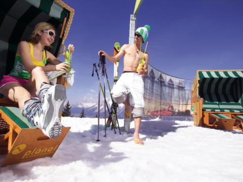 Paar trinkt Cocktails am Planai Beach mit Strandkörben im Skigebiet Planai-Hochwurzen. JUFA Hotels bietet erholsamen Familienurlaub und einen unvergesslichen Winterurlaub.