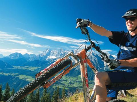 Sie sehen einen Mountainbiker auf der Planai mit dem Dachstein im Hintergrund.JUFA Hotels bietet Ihnen den Ort für erlebnisreichen Natururlaub für die ganze Familie.