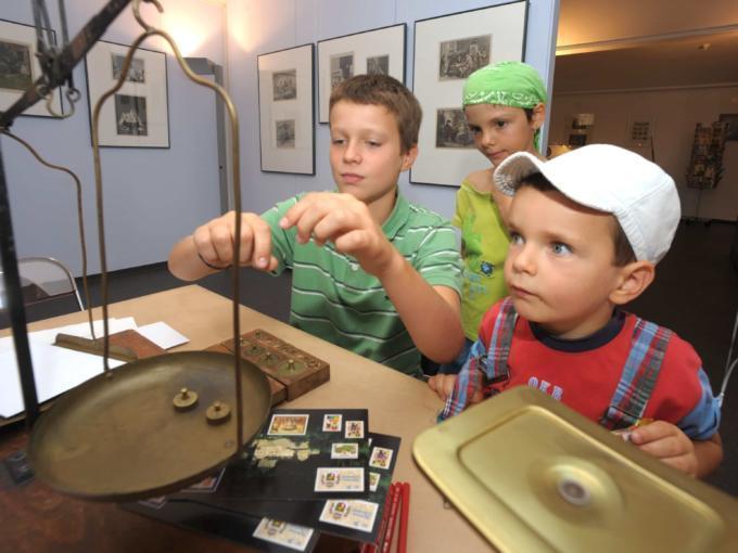 Sie sehen Kinder im Postmuseum in Vaduz beim wiegen von Gewichten. JUFA Hotels bietet kinderfreundlichen und erlebnisreichen Urlaub für die ganze Familie.