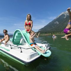 Familie beim Trettbootfahren auf dem Presseggersee in Nassfeld in Kärnten in der Nähe von JUFA Hotels. Der Ort für erholsamen Familienurlaub und einen unvergesslichen Winter- und Wanderurlaub.