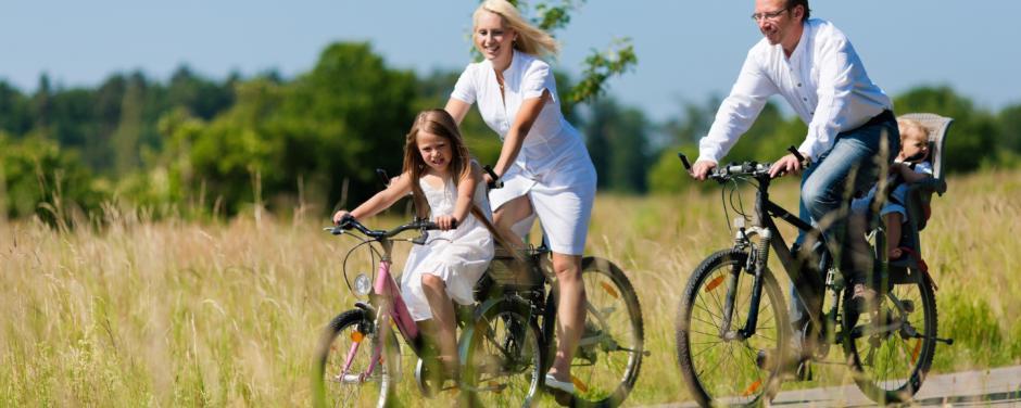 Familie fährt Fahrrad auf einem Radweg durch sommerliche Landschaft in der Nähe von JUFA Hotels. Der Ort für erholsamen Familienurlaub und einen unvergesslichen Winter- und Wanderurlaub.