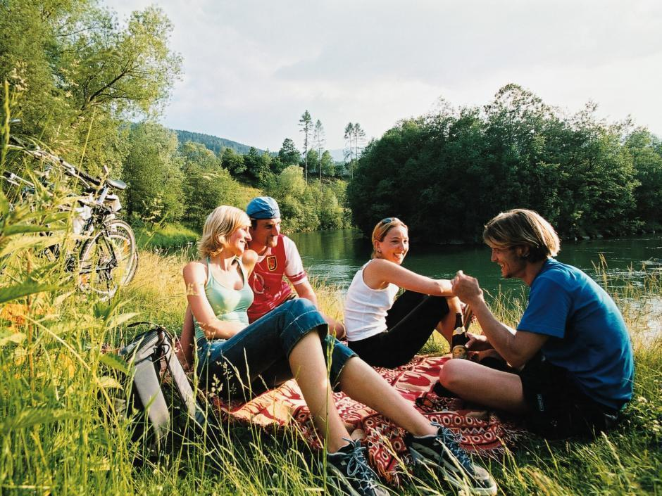 Radler rasten am Murradweg auf Wiese. JUFA Hotels bietet erholsamen Familienurlaub und einen unvergesslichen Winter- und Wanderurlaub.