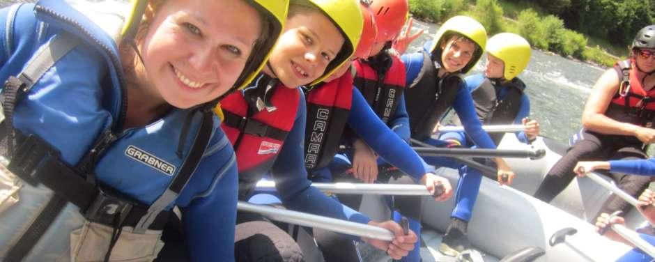 Kinder und Erwachsene haben viel Spaß beim Rafting in der Natur. JUFA Hotels bietet erlebnisreiche Feriencamps in den Bereichen Sport, Gesundheit, Bildung und Sprachen.
