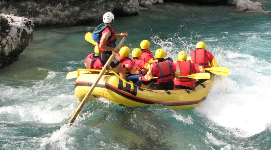 Menschen in einem Schlauchboot beim Rafting mit viel Action. JUFA Hotels bietet erlebnisreiche Feriencamps in den Bereichen Sport, Gesundheit, Bildung und Sprachen.