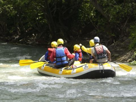 Menschen in einem Schlauchboot beim Rafting in wunderschöner Natur. JUFA Hotels bietet erlebnisreiche Feriencamps in den Bereichen Sport, Gesundheit, Bildung und Sprachen.