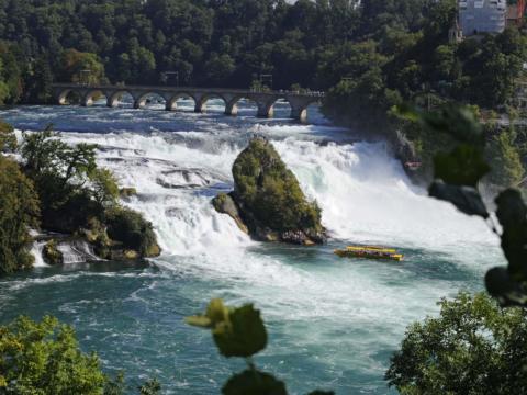 Rheinfall im Kanton Schaffhausen in der Schweiz mit Ausflugsboot im Sommer. Der Ort für erholsamen Familienurlaub und einen unvergesslichen Winter- und Wanderurlaub.