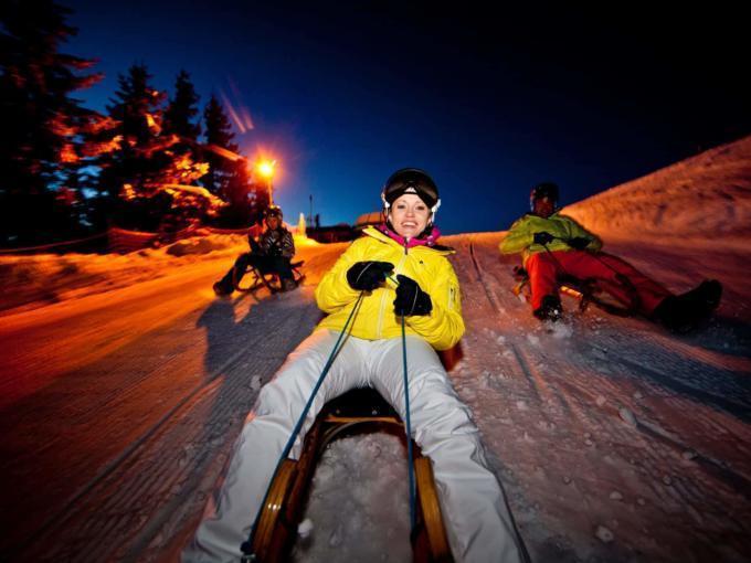 Familie beim Nachtrodeln auf der Hochwurzen in der Steiermark. JUFA Hotels bietet erholsamen Familienurlaub und einen unvergesslichen Winterurlaub.