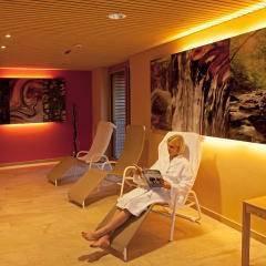 Eine Frau im Bademantel sitzt im Liegestuhl und liest eine Zeitschrift im Ruheraum im Wellnessbereich im JUFA Hotel Almtal. Der Ort für erholsamen Familienurlaub und einen unvergesslichen Winter- und Wanderurlaub.