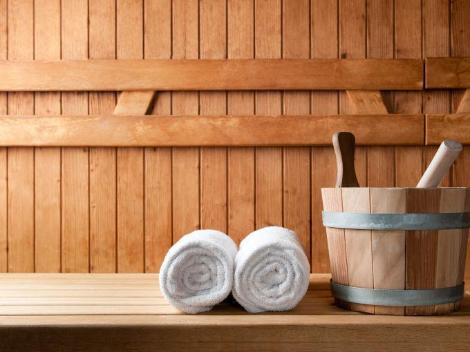 Sauna mit Aufgusskübel und gerollten Handtüchern. JUFA Hotels bietet erholsamen Thermenspass für die ganze Familie.