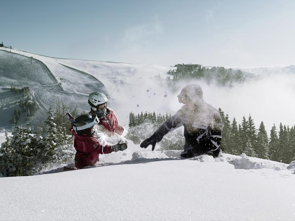 Sie sehen spielende Kinder im Schnee mit Schneeschuhen und Berge im Hintergrund auf der Schmitten. JUFA Hotels bietet erholsamen Familienurlaub und einen unvergesslichen Winterurlaub.