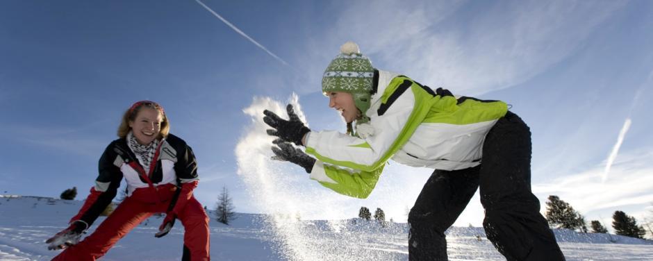 Frauen toben im Schnee bei Sonnenschein im Winter. JUFA Hotels bietet erholsamen Familienurlaub und einen unvergesslichen Winterurlaub.