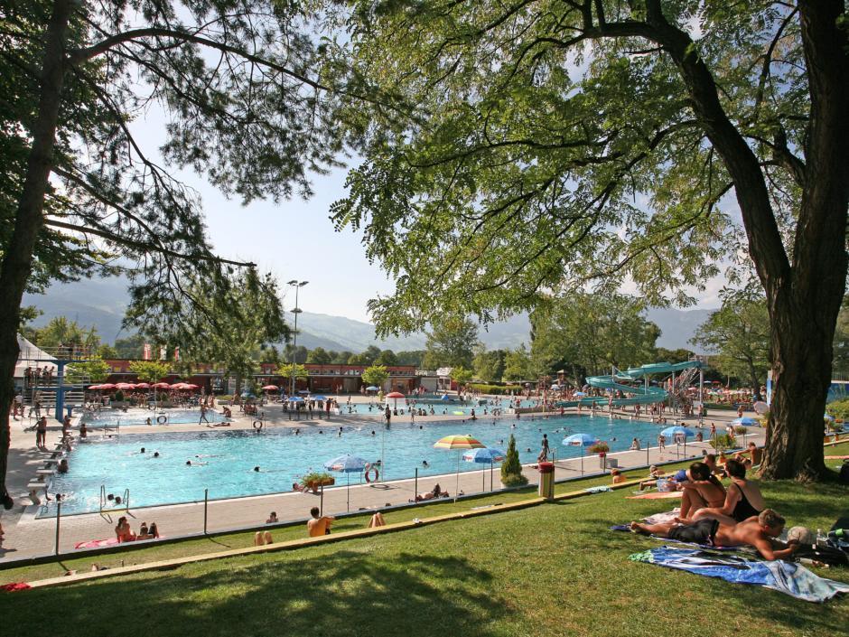 Schwimmbad Mühleholz mit Badegästen in Vaduz in Liechtenstein in der Nähe vom JUFA Hotel Malbun - Alpin-Resort. Der Ort für erholsamen Familienurlaub und einen unvergesslichen Winter- und Wanderurlaub.
