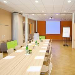 Seminarraum mit Besprechungstisch im JUFA Hotel Bleiburg Sport-Resort. Der Ort für erholsamen Familienurlaub und einen unvergesslichen Winter- und Wanderurlaub.