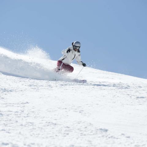 Skifahrerin fährt die Skipiste herunter am Golm in Vorarlberg. JUFA Hotels bietet erholsamen Familienurlaub und einen unvergesslichen Winterurlaub.