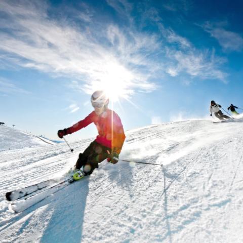 Skifahrer auf der Piste im Skigebiet Lachtal bei wunderbarem Wetter. JUFA Hotels bietet erholsamen Familienurlaub und einen unvergesslichen Winterurlaub.