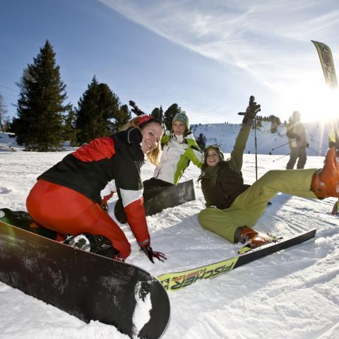 Skifahrer und Snowboarder liegen auf der Piste im Skigebiet Kreischberg in der Nähe von JUFA Hotels. Der Ort für erholsamen Familienurlaub und einen unvergesslichen Winterurlaub.
