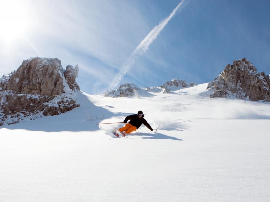 Mann beim Skifahren am Obertauern im Salzburger Land bei Sonnenschein. JUFA Hotels bietet erholsamen Familienurlaub und einen unvergesslichen Winterurlaub.