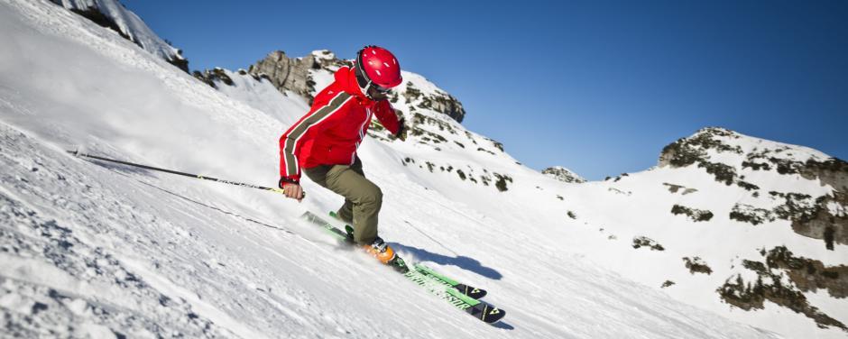 Skifahrer fährt im Skigebiet Loser Sandling im Salzkammergut die Piste herunter in der Nähe von JUFA Hotels. Der Ort für erholsamen Familienurlaub und einen unvergesslichen Winter- und Wanderurlaub.