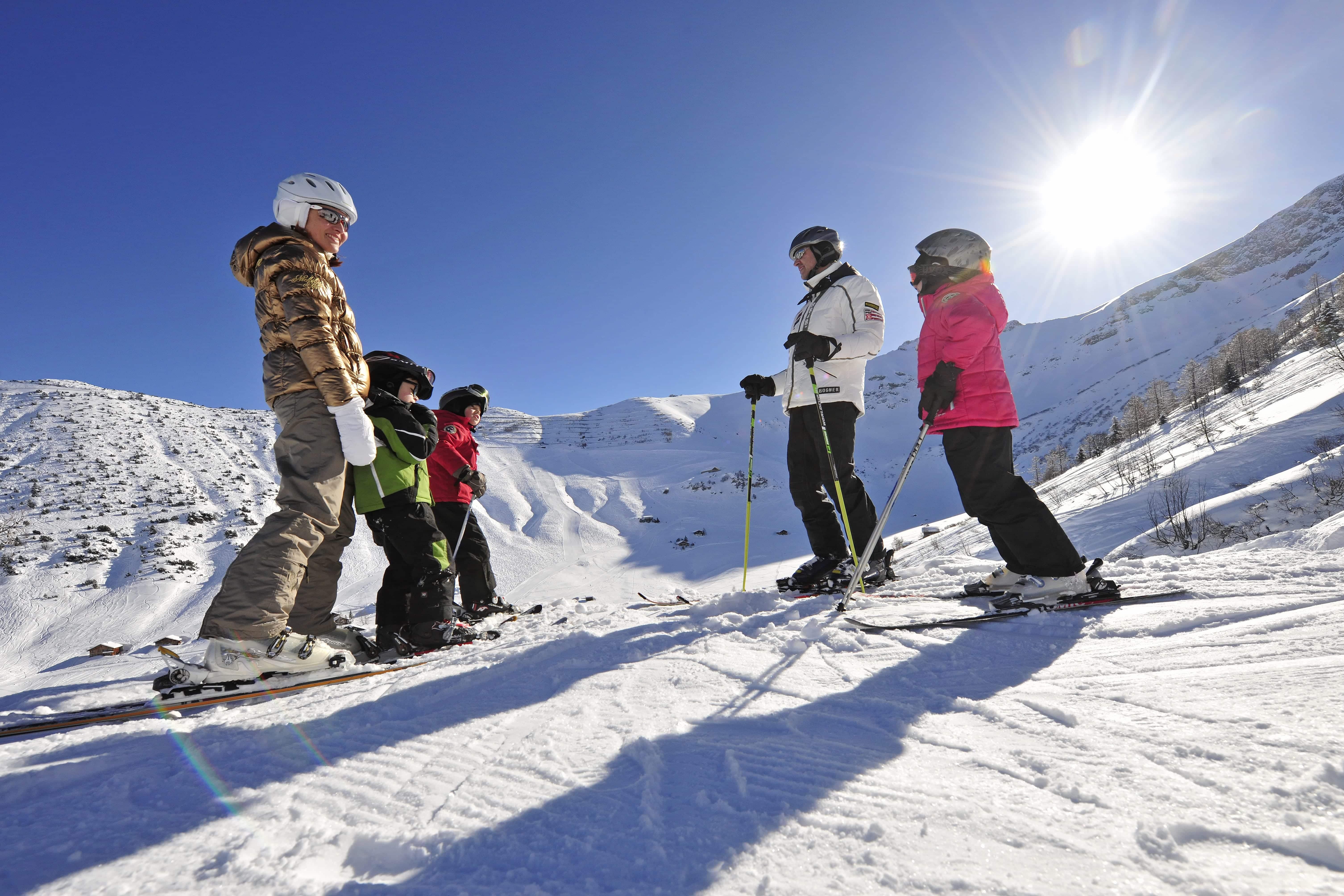 Familie beim Skifahren im Skigebiet Malbun in den Liechtensteiner Alpen in der Nähe vom JUFA Hotel Malbun - Alpin-Resort. Der Ort für erholsamen Familienurlaub und einen unvergesslichen Winterurlaub.