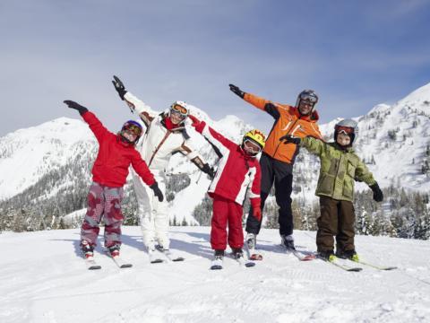 Familie macht Aufwärmübungen auf Skiern im Skigebiet Nassfeld in Kärnten in der Nähe von JUFA Hotels. Der Ort für erholsamen Familienurlaub und einen unvergesslichen Winter- und Wanderurlaub.