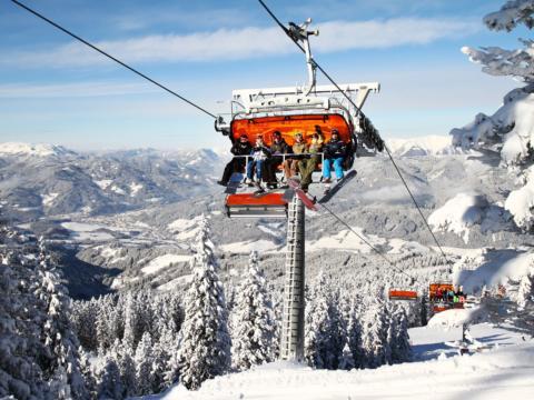 Snowboarder auf Sessellift im Skigebiet Semmering-Stuhleck in Niederösterreich. JUFA Hotels bietet erholsamen Familienurlaub und einen unvergesslichen Winterurlaub.