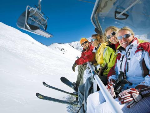 Skifahrer fahren mit dem Sessellift im Skigebiet Tauplitzalm bei Sonnenschein. JUFA Hotels bietet erholsamen Familienurlaub und einen unvergesslichen Winterurlaub.