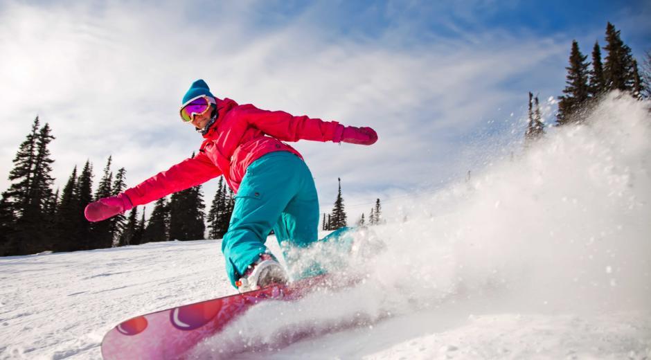 Snowboarder kurvt die Piste mit Pulverschnee herunter in der Nähe von JUFA Hotels. Der Ort für erholsamen Familienurlaub und einen unvergesslichen Winterurlaub.