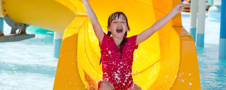 Mädchen rutscht auf gelber Wasserrutsche in einem Freibad in der Nähe von JUFA Hotels. Der Ort für erholsamen Familienurlaub und einen unvergesslichen Winter- und Wanderurlaub.