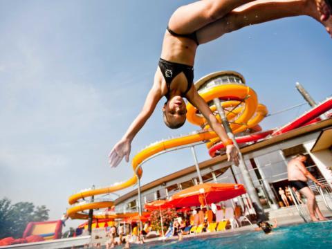 Mädchen macht einen Kopfsprung ins Becken der Sonnentherme Lutzmannsburg. JUFA Hotels bietet Ihnen den Ort für erlebnisreichen Natururlaub für die ganze Familie.