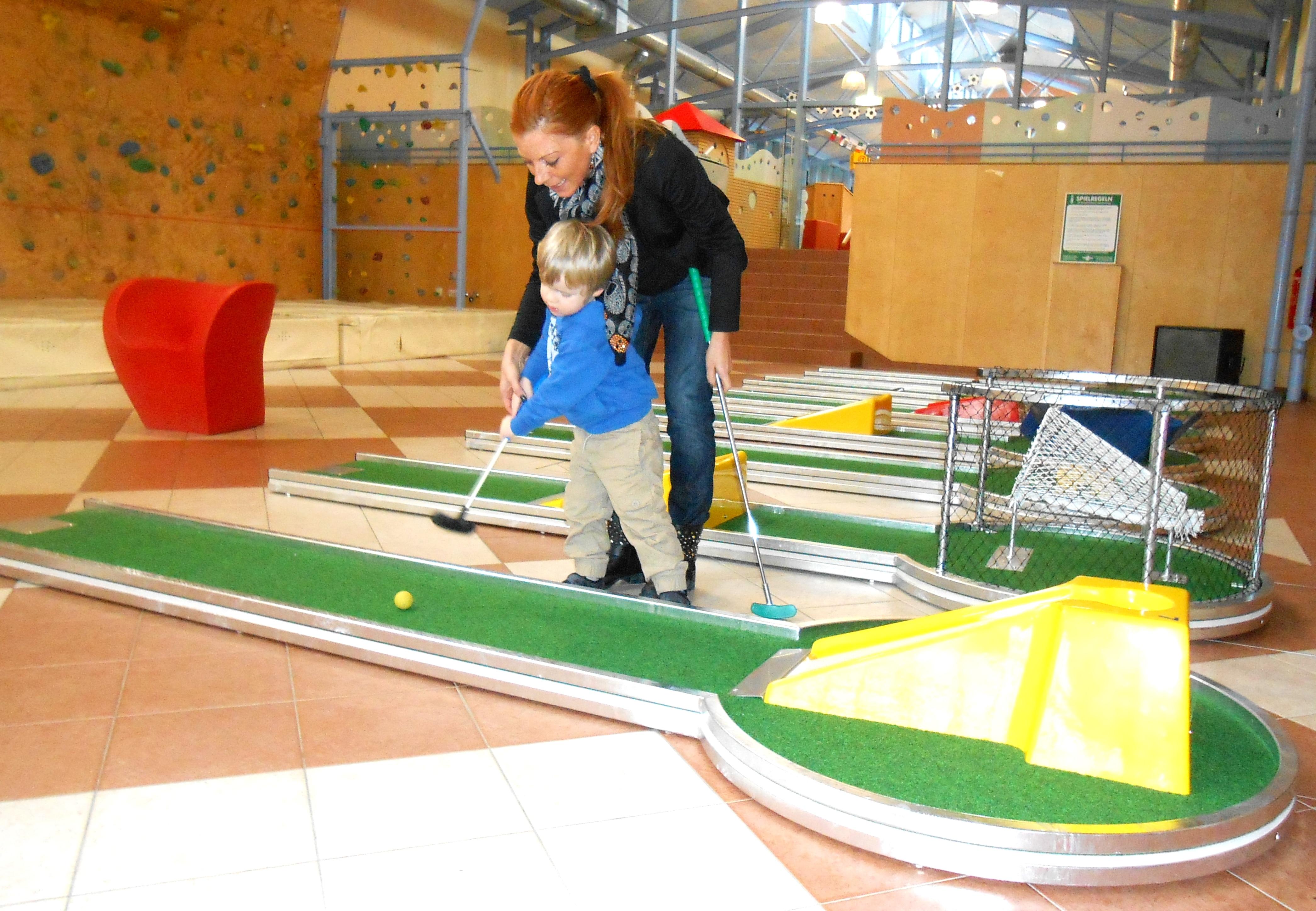 Mutter und Kind spielen Mini-Golf im Indoorspielbereich im JUFA Hotel Gnas - Sport-Resort. Der Ort für erfolgreiches Training in ungezwungener Atmosphäre für Vereine und Teams.