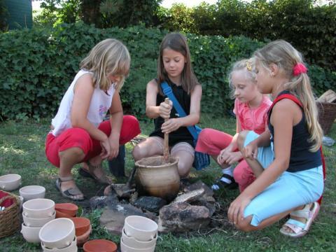 Kinder beim Töpfern im Garten des Steinzeit Töpfereimuseum Langerwehe. JUFA Hotels bietet kinderfreundlichen und erlebnisreichen Urlaub für die ganze Familie.