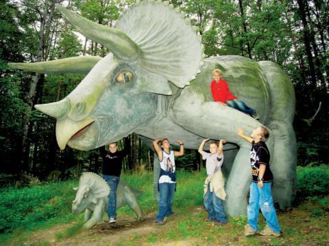 Kinder stehen vor Dinosauria im Styrassic Park in der Nähe von JUFA Hotels. Der Ort für erholsamen Familienurlaub und einen unvergesslichen Winter- und Wanderurlaub.